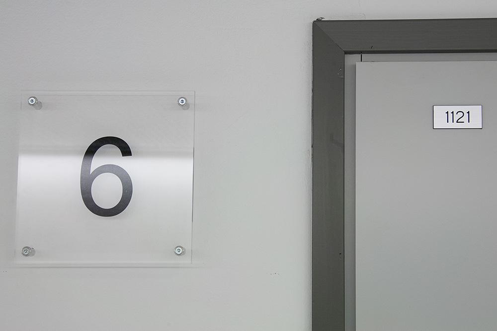 Huonenumerointi oveen. Taustalle teipattu tarrateksti. Kiinnitys läpiruuvein.