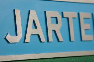 Alumiinikyltti. Logo ja teksti jyrsitty koholle 5mm alumiinilevyyn. Viimeistelynä pohjan ylimaalaus siniseksi, tekstit ja kehys hiottu.