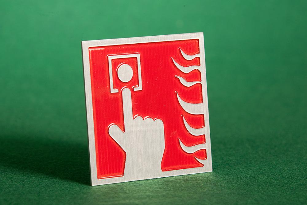 Turva- ja ohjekilpi. palohälytin-symboli on jyrsitty koholle alumiinilevyyn. Pohja ylimaalattu punaiseksi, tekstit ja kehys hiottu. Viimeistelynä lakkaus.