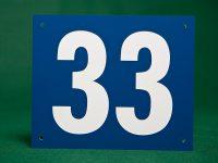 Muovista valmistettu numerointi. Materiaali kaksikerrosmuovia, numero kaiverrettu.