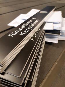 Mustaan kaiverrusmuoviin kaiverrettuja postilaatikon nimikylttejä