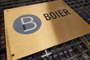 Yrityksen nimi messinkikilvessä. Tarrasta tehty logo, kilpi hiottu ja lakattu.
