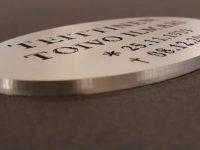 Nimilaatta hautakiveen on kaiverrettu alumiinista. Kaiverrus maalattu ja nimilaatta hiottu.