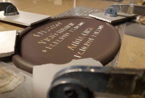 Lisäkaiverrus vanhaan hautalaattaan. Hautakilpeen on kaiverrettu sekä vanha, että uusi teksti.