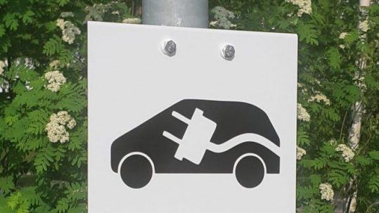 Autopaikkakyltti sähköauton latauspisteestä valkoisella kantatulla alumiinipohjalla, tarrateksti