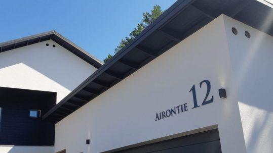 Talonumeroon on yhdistetty kadunnimi, materiaali harmaaksi maalattu alumiini-irtokirjaimet.