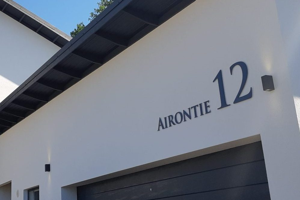 Talon numero ja kadunnimi on valmistettu grafiitin harmaaksi maalatusta alumiinista. Kiinnitys seinään koroketapeilla.