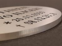 Muistolaatta luonnonväriin anodisoitua alumiinia. Tekstit kaiverrettu ja maalattu.
