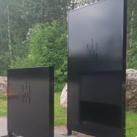 Opastevitriini mustaksi maalattua alumiinia, taustalla logo.