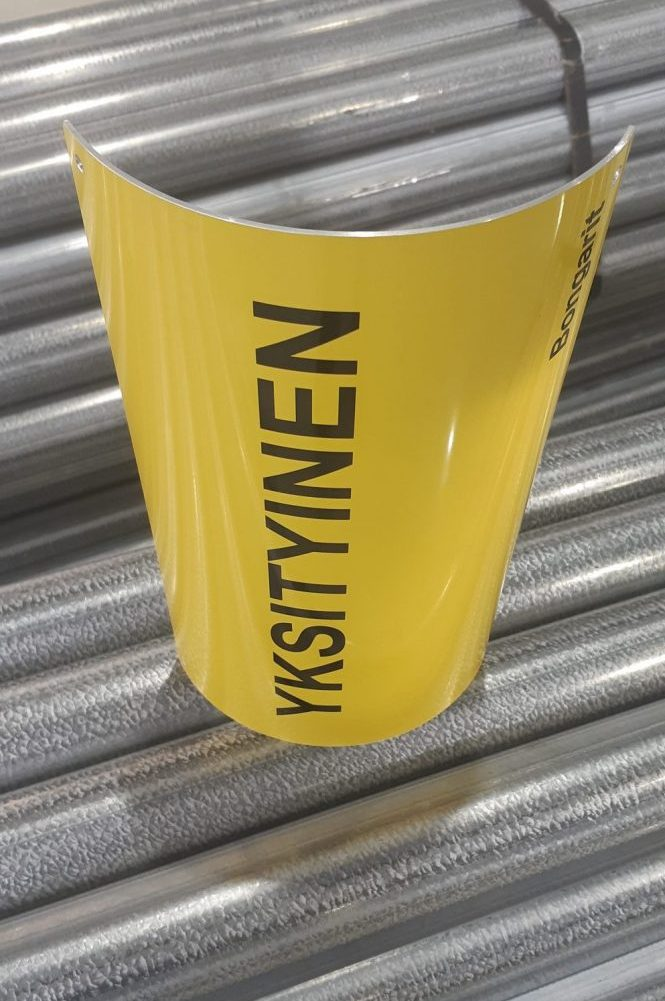 Yksityinen -merkki keltaista alumiinia. Alumiini taivutettu istumaan kaarevaan pintaan, tekstit teipattu.