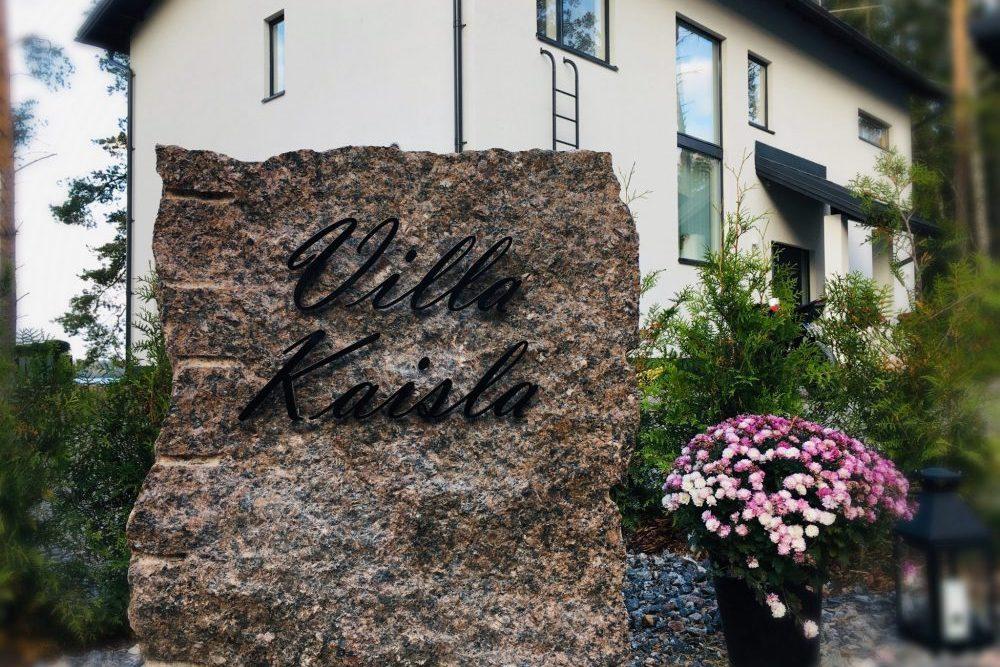 Talon nimikyltti harmaaksi maalattua alumiinia. Talo Villa Kaisla.