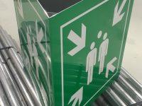 Kolmisivuinen koontumispaikkakyltti vihreää alumiinia, kuviot tarraa.