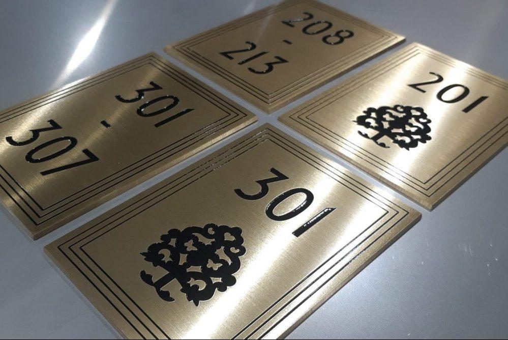 Materiaali 3 mm hiottu ja suojalakattu messinki. Kehykset, numero ja kuvio kaiverrettu ja maalattu mustaksi