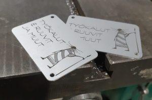 Tekstit ja kuva on lasermerkattu alumiinikyltteihin.
