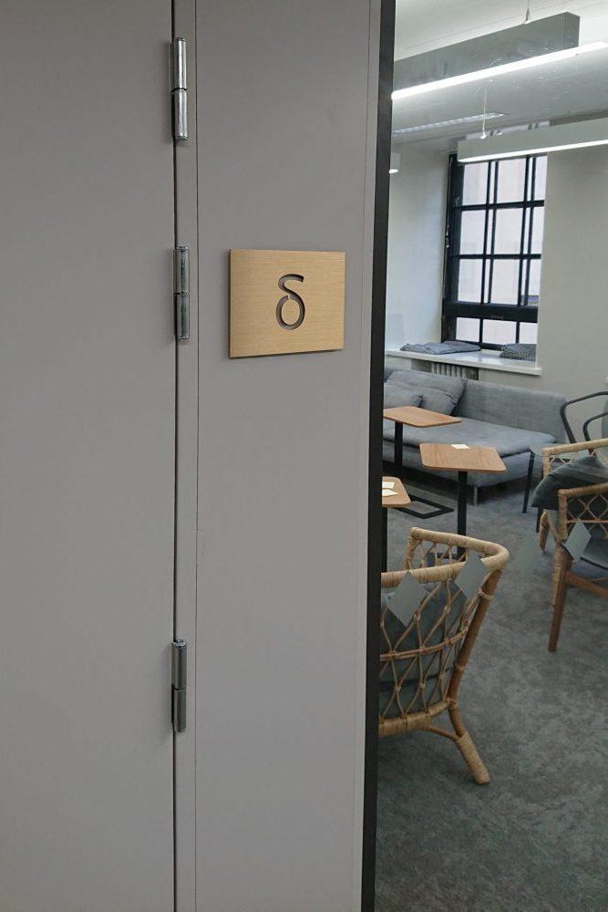 Neuvottelutilan nimikyltti aukileikattua messinkiä. Kiinnitetty pintaan akryylikorokkeilla ja kaksipuoleisella tarralla.